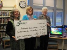 (L-R) Louise Capizzo, Library Youth Services Manager, accepts a check in support of the Library's Early Literacy Stations (seen in background) from Melanie Lee, SBSI Scarborough Branch Manager, and Terri Litchfield, SBSI Scarborough Branch Teller.